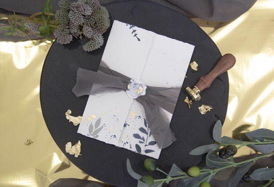 A imagem mostra o convite de casamento fechado, vendo-se o tecido em volta fechado por um lacre.